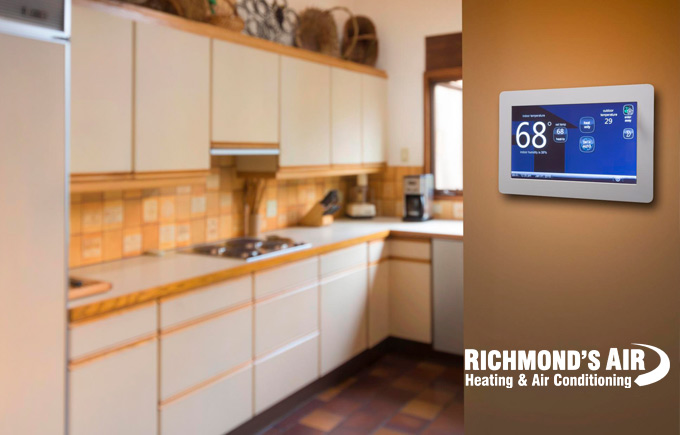 close-up of home thermostat with kitchen in the background